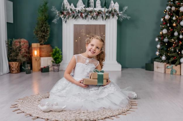 Bambina con un regalo in mano su uno sfondo sullo sfondo di decorazioni natalizie.