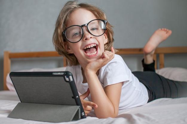 La bambina con gli occhiali fa i compiti online sdraiata sul letto a casa comunicazione con i parenti