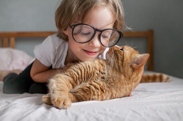 La bambina con gli occhiali giace sul letto e abbraccia un grasso gatto allo zenzero