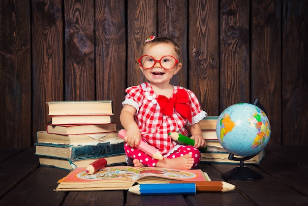 Bambina con occhiali e matite
