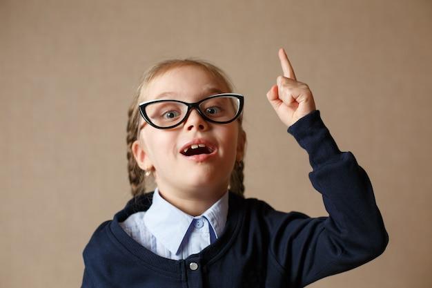 Una bambina con gli occhiali alzò il dito. concetto dell'idea