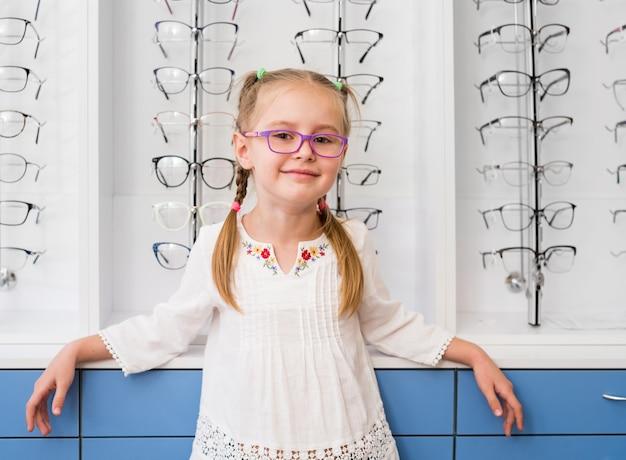 Bambina con gli occhiali in piedi nel negozio di ottica