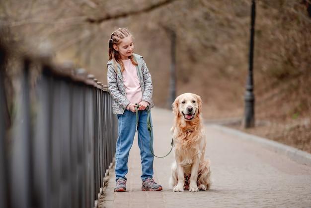Bambina con cane golden retriever fuori