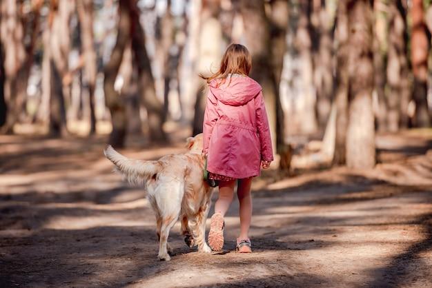 Bambina con cane golden retriever nel bosco