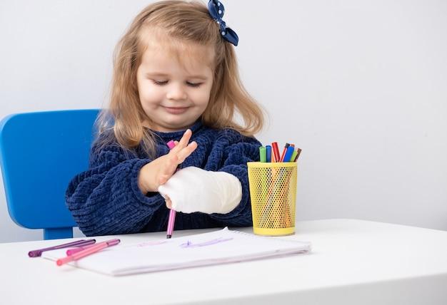 Bambina con la mano nel cast seduto al tavolo cercando di disegnare con i pennarelli.
