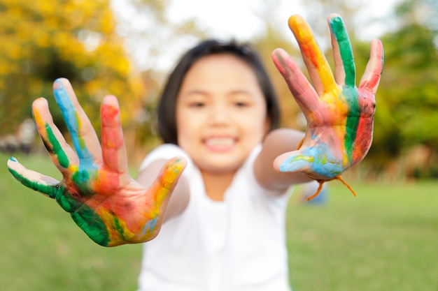 Bambina con le mani dipinte in vernice colorata
