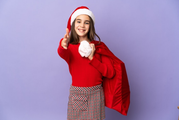 Bambina con cappello e sacco di natale isolato su sfondo viola si stringono la mano per chiudere un buon affare