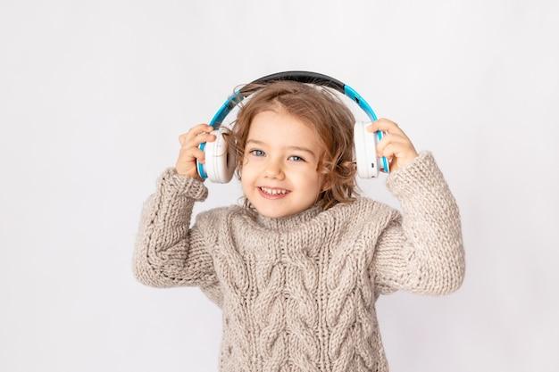 Bambina con le cuffie su uno sfondo bianco ascoltando musica e godersi lo spazio per il testo