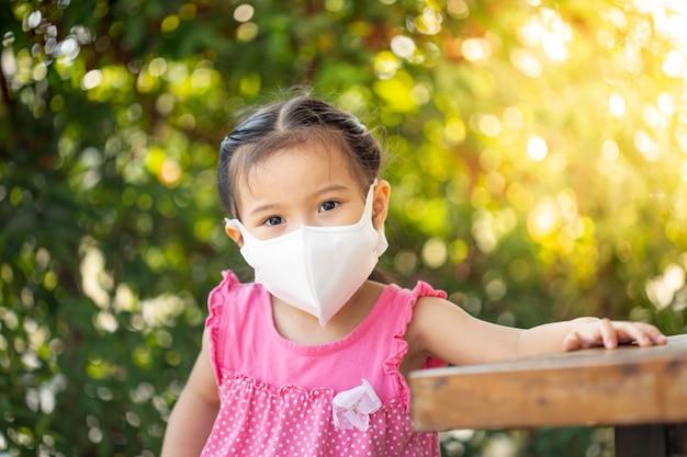 La bambina con la mascherina di salute protegge il virus della corona.
