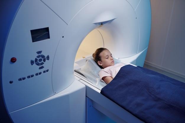 Bambina con gli occhi chiusi che si muove nella macchina per la risonanza magnetica