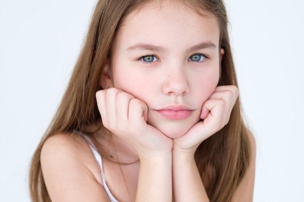 Bambina con le mani appoggiate sotto il mento sul muro bianco.