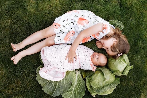 Bambina con la sorella appena nata sono sdraiati sull'erba con cavoli all'aperto