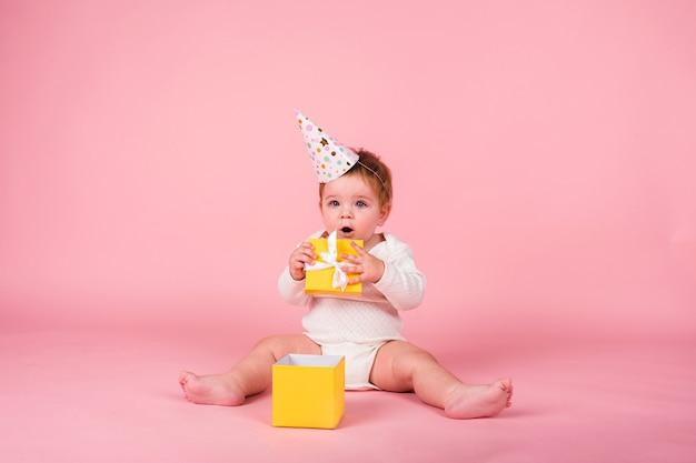 Una bambina con un cappello da festa si siede con una scatola gialla su una parete rosa