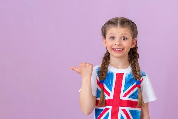 Una bambina con l'immagine della bandiera inglese su una maglietta punta il dito a lato del tuo annuncio. copia spazio.