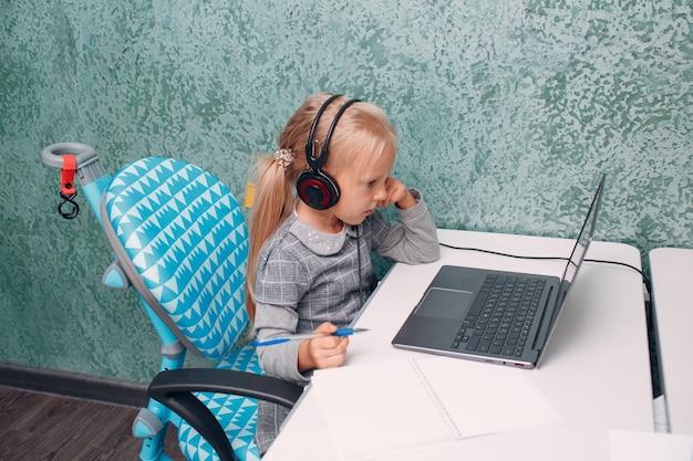 Bambina con il computer portatile che impara e si prepara al ritorno a scuola