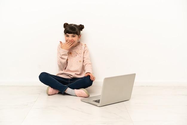 Bambina con un computer portatile che si siede sul pavimento felice e sorridente che copre la bocca con la mano
