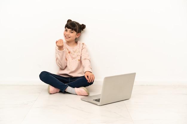 Bambina con un laptop seduto sul pavimento che invita a venire con la mano. felice che tu sia venuto