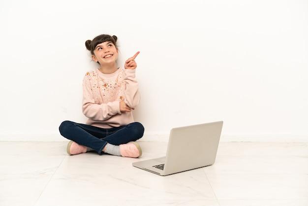Bambina con un laptop seduto sul pavimento che indica una grande idea