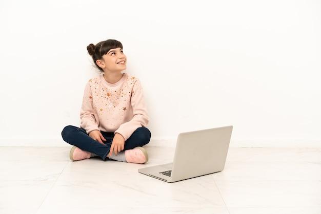 Bambina con un computer portatile che si siede sul pavimento che pensa un'idea mentre osserva in su