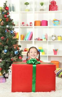 Bambina con grande confezione regalo vicino all'albero di natale