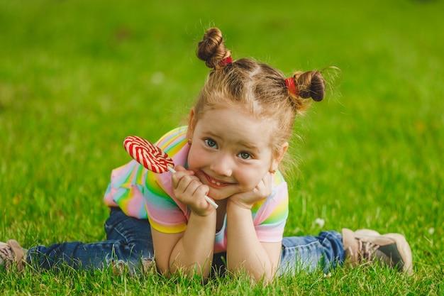 La bambina con il lecca-lecca si siede sull'erba in estate nel parco