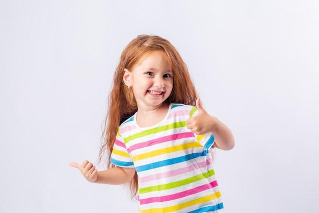 La bambina con i capelli rossi lunghi sta sorridendo in una maglietta multicolore