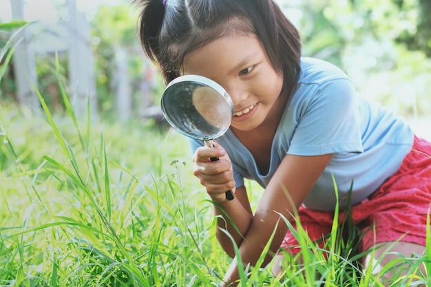 Bambina con lente di ingrandimento in natura