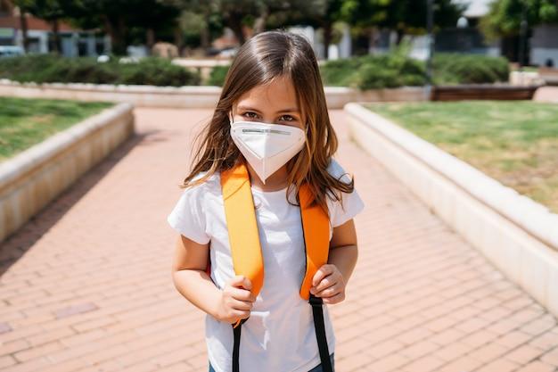 Bambina con la maschera in un parco durante la pandemia di coronavirus