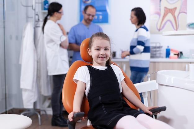 Bambina con dente mancante che si siede sulla sedia nell'ufficio del dentista che sorride alla macchina fotografica. bambino con sua madre durante il controllo dei denti con stomatolog seduto su una sedia.