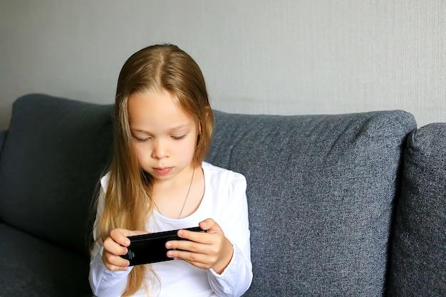 Bambina con un telefono cellulare e tiene tra le mani e lo guarda.