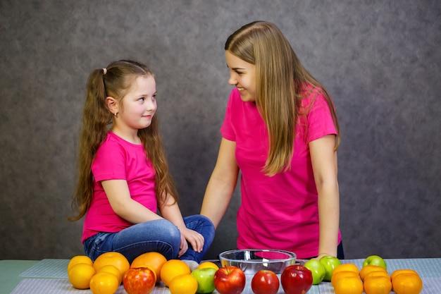 La bambina con la mamma gioca con la frutta e sorride. vitamine e alimentazione sana per i bambini.