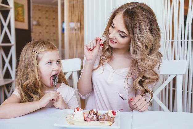 Bambina con la madre che mangia il gelato in un accogliente caffè. buon rapporto di genitori e figli.