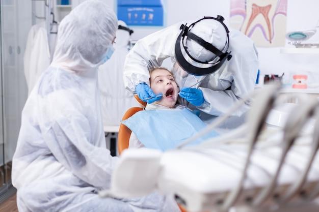 Bambina con la bocca aperta che ottiene il trattamento della carie dal dentista pediatrico vestita in tuta dpi. dentista in tuta da coronavirus che utilizza uno specchio curvo durante l'esame dei denti del bambino.