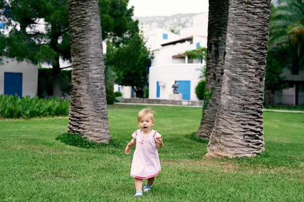La bambina con la bocca aperta cammina su un prato verde sullo sfondo di enormi palme da datteri