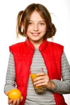 Bambina con arance e succo. isolato su bianco.
