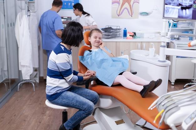 Bambina con espressione dolorosa a causa della cavità del dente in attesa di trattamento dal dentista professiona. bambino con sua madre durante il controllo dei denti con stomatolog seduto su una sedia.