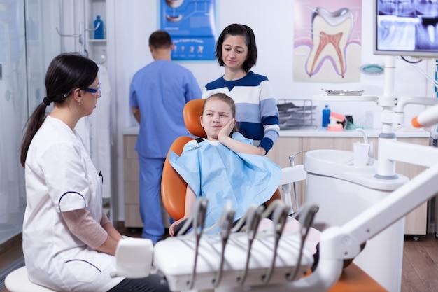 Bambina con l'espressione dolorosa che mostra al dentista dove il suo dente fa male durante il controllo dentale. bambino con sua madre durante il controllo dei denti con stomatolog seduto su una sedia.