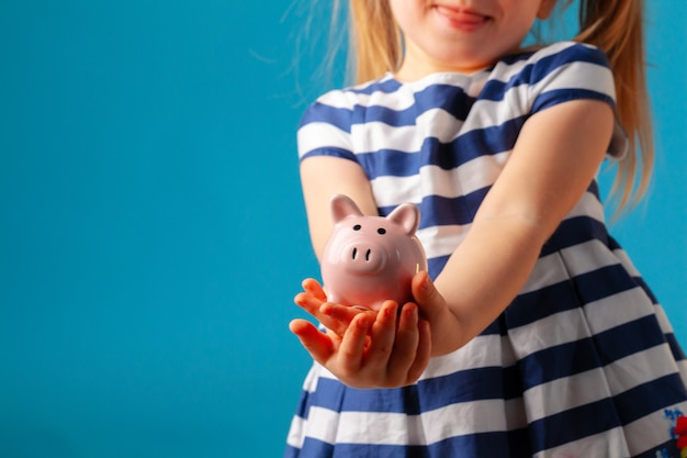 Bambina con salvadanaio salvadanaio su sfondo blu