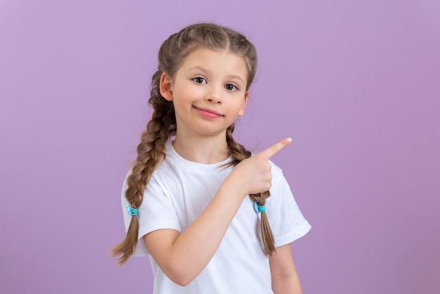 Una bambina con le trecce e una maglietta bianca indica il lato su sfondo viola