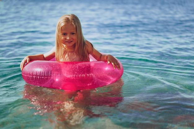 Bambina con cerchio gonfiabile rosa che bagna nel mare