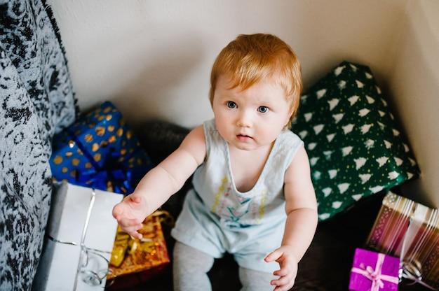 Una bambina con i regali si siede sui regali di sfondo