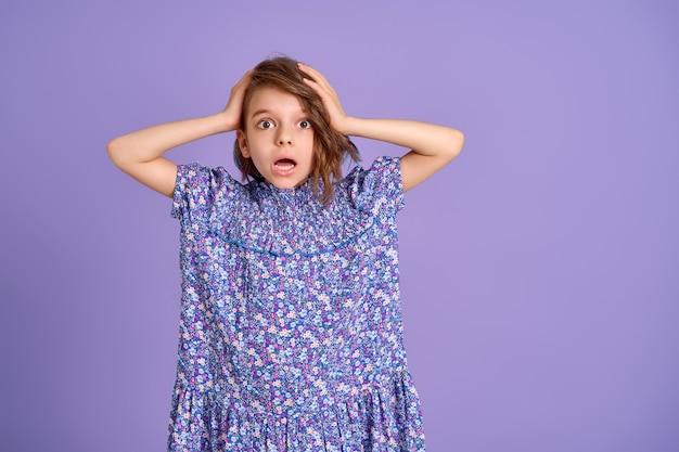 Bambina con vestito viola che sembra sorpresa e scioccata su sfondo viola