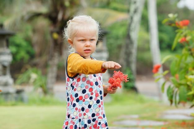 Bambina con fiori rossi in giardino tropicale