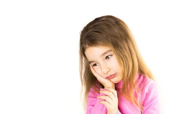 La bambina con la faccia triste tiene la sua guancia con la mano - il dente fa male