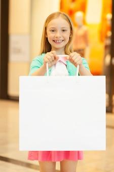 Bambina con borsa della spesa. bambina allegra che tiene in mano la borsa della spesa e sorride alla telecamera mentre si trova in un centro commerciale