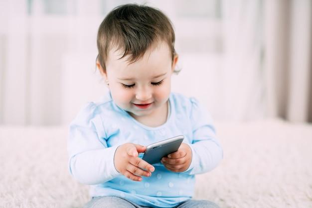 Una bambina con un telefono smartphone in mano si siede e preme