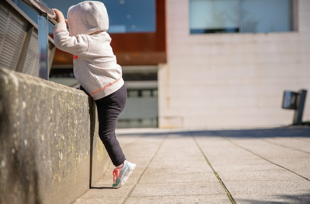 Bambina con scarpe da ginnastica e felpa con cappuccio che si allena duramente con una ringhiera di metallo in una piazza della città