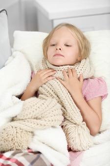 Bambina con mal di gola sdraiato sul letto