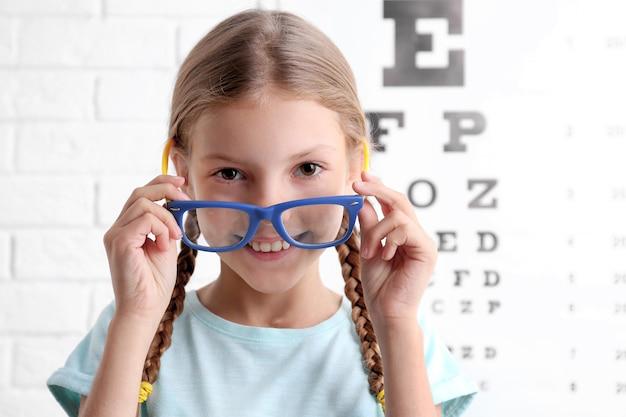 Bambina con gli occhiali sul diagramma di prova oftalmico