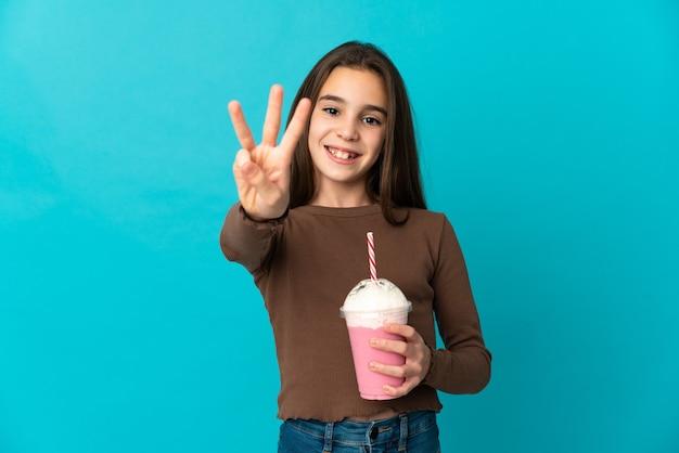 Bambina con frullato di fragole isolato su sfondo blu felice e contando tre con le dita